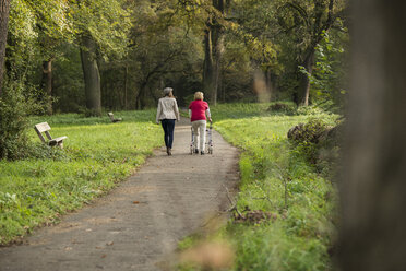 Senior woman and granddaughter walking together in a park, back view - UUF002573