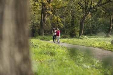 Senior woman and granddaughter walking together in a park - UUF002574