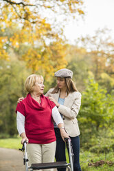 Senior woman and her caring adult granddaughter walking together in autumnal park - UUF002585