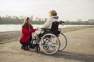 Adult granddaughter assisting her grandmother sitting in wheelchair - UUF002591