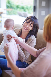 Mother holding her baby with woman holding baby clothes - ZEF002279