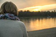 Senior woman watching sunset, back view - UUF002622