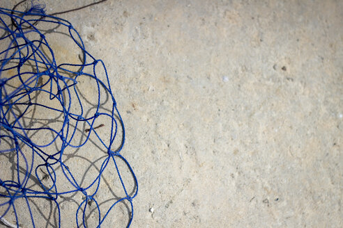 Part of blue net on stone floor - CMF000194