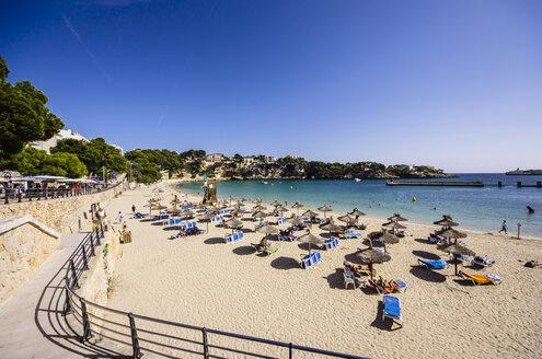 Spain, Mallorca, Porto Cristo, Beach with sunshades and beach loungers - THAF000858