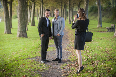 Young businesswoman photographing  business partners with her smartphone in a park - PAF001073