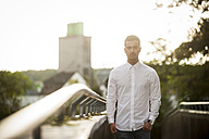 Serious looking young man wearing white shirt standing at backlight - PAF001076