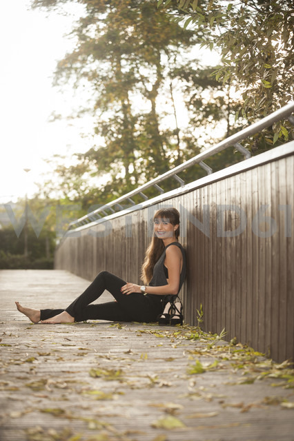 Smiling young woman relaxing on a footbridge - PAF001084 - Andreas Pacek/Westend61