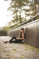 Smiling young woman relaxing on a footbridge - PAF001084