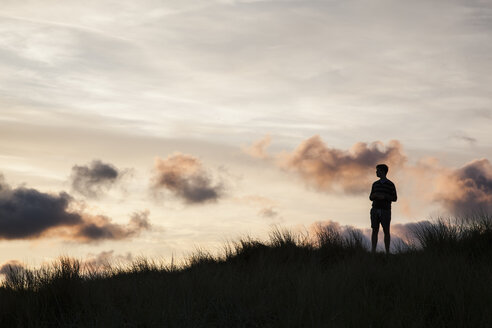 Silhouette of teenage boy standing on beach dune in front of evening twilight - MVC000140