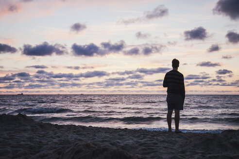 Silhouette of teenage boy standing on beach looking at the sea in front of evening sky - MVC000142