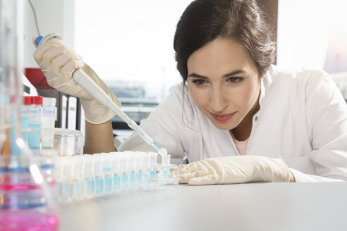 Female researcher working with test tubes in laboratory - FKF000838