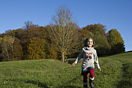 Germany, Bavaria, Landshut, girl running on meadow in autumn - YFF000258