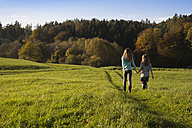 Germany, Bavaria, Landshut, two girls walking on meadow in autumn - YFF000260