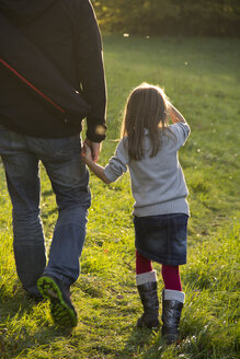 Germany, Bavaria, Landshut, father and daughter walking on meadow in autumn - YFF000265
