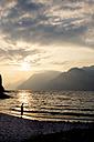 Italy, Veneto, Malcesine, Boy standing at Lake Garda in evening light - LVF002169
