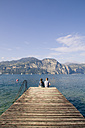 Italy, Veneto, Malcesine, Brothe and sister sitting on jetty - LVF002163