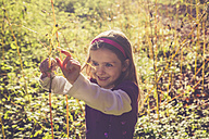Little girl playing with jewelweed in the wood - SARF000999