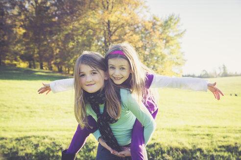 Girl giving another little girl a piggyback - SARF001009