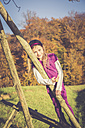 Portrait of smiling little girl leaning on wooden bar in front of autumn forest - SARF001017