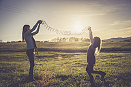 Two little girls playing with a spiral on a meadow in backlight - SARF001016