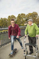 Happy senior man with wheeled walker and adult grandson with skateboard - UUF002649