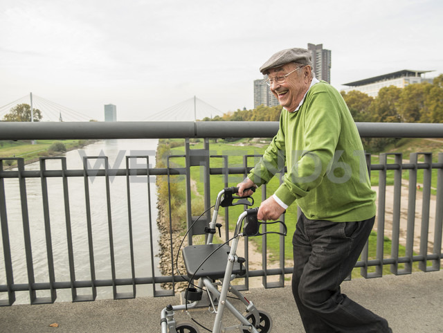 Playful senior man with wheeled walker on bridge - UUF002652