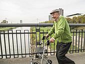 Playful senior man with wheeled walker on bridge - UUF002652