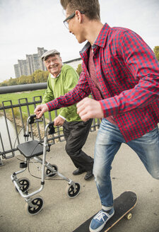 Happy senior man with wheeled walker and adult grandson with skateboard - UUF002654