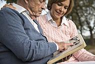 Senior man and daughter looking at photo album - UUF002667