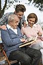 Senior man with grandson and daughter looking at photo album - UUF002725