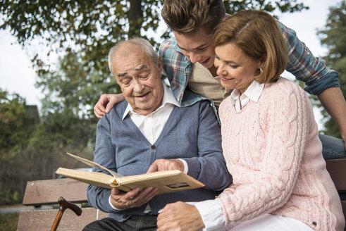 Senior man with grandson and daughter looking at photo album - UUF002669