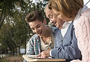 Senior man with grandson and daughter looking at photo album - UUF002671