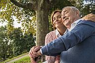 Daughter embracing senior man outdoors - UUF002682