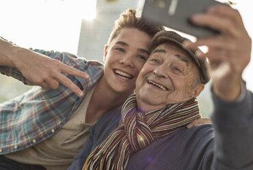 Happy senior man taking a selfie with grandson - UUF002719