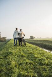 Senior man and grandson in rural landscape with bicycle - UUF002699