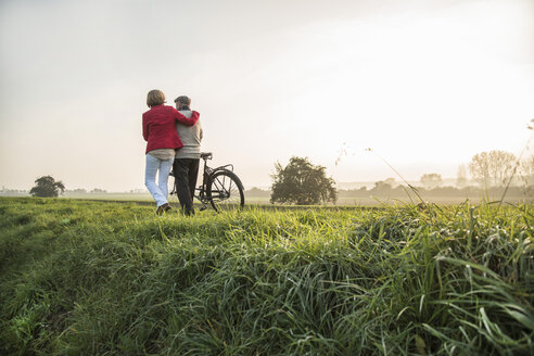 Senior man and daughter in rural landscape with bicycle - UUF002703