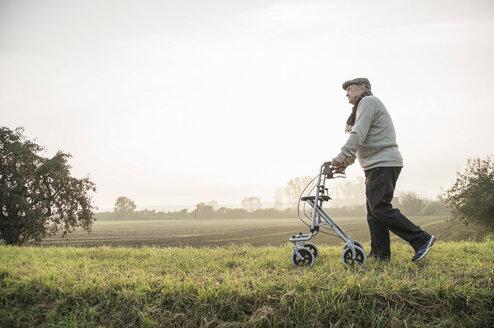 Senior man with wheeled walker walking in rural landscape - UUF002705