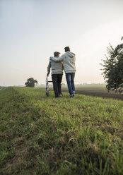 Senior man and grandson in rural landscape with wheeled walker - UUF002707