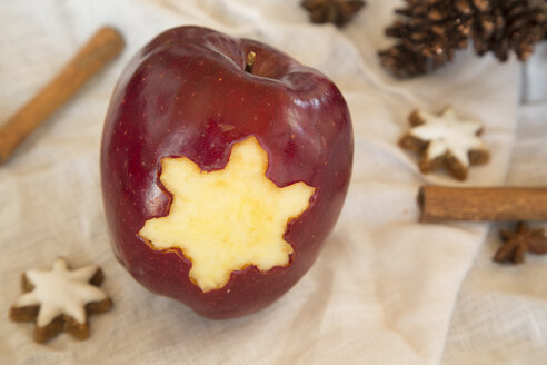 Red apple with star shaped hole, cinnamon stars, cinnamon sticks and fir cones on cloth - SARF001028