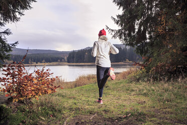 Germany, Thuringia, woman running through the forest by the lake near Alsbach - VTF000348
