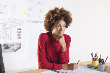 Portrait of smiling young female architect sitting at her desk - EBSF000334