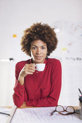 Portrait of smiling young female architect with cup of coffee at her desk - EBSF000338