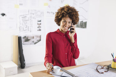 Portrait of smiling young female architect telephoning with smartphone at her office - EBSF000341