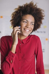 Portrait of smiling young female architect telephoning with smartphone - EBSF000346