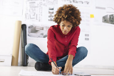 Young female architect working on the floor of her office - EBSF000359