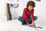 Young female architect working on the floor of her office - EBSF000361