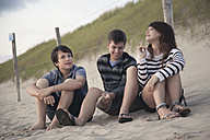 Netherlands, three teenagers relaxing on the beach - MVC000146