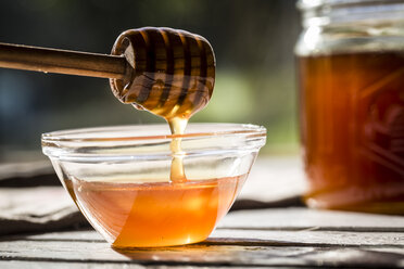 Honey dripping off a honey spoon into a glass bowl - SARF001031