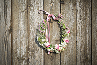 Self-made floral wreath with rose blossoms and Gypsophila hanging at wooden wall - ASCF000009