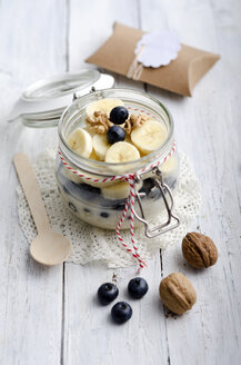 Preserving jar of watered oat flakes, banana slices, blueberries and walnuts - ODF000863